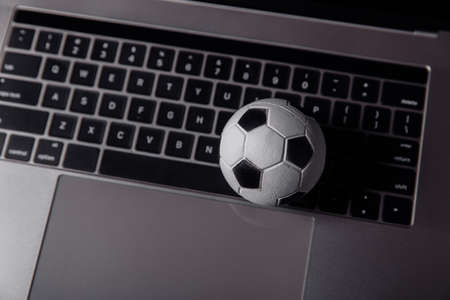 Soccer ball on a laptops keyboard. Sport, gambling, money win concept