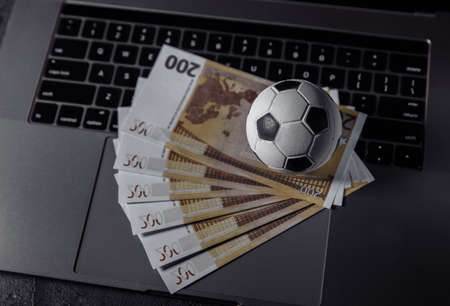 Soccer ball and euro banknotes on a keyboard. Sport, gambling, money win concept