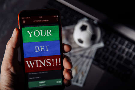 Man holding smartphone with winning result of his bet. Close-up