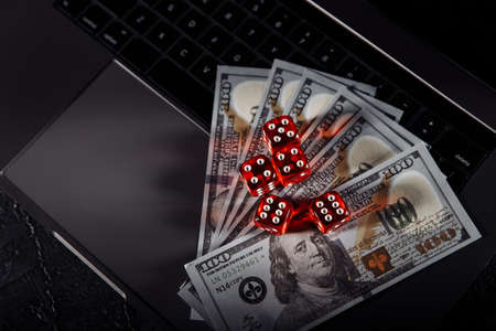 Dice and dollar banknotes on laptops keyboard. Online casino and gambling concept