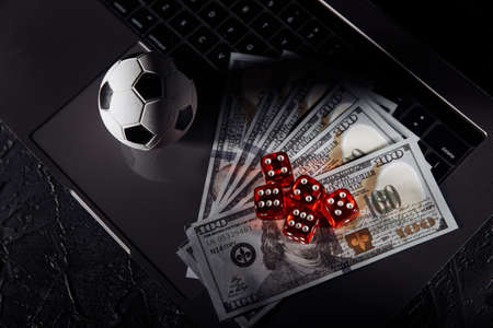 Dice, soccer ball and dollar banknotes on laptops keyboard. Gambling and betting concept Stok Fotoğraf