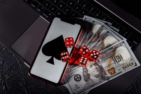 Dice, smartphone and dollar banknotes on keyboard. Online casino and gambling concept