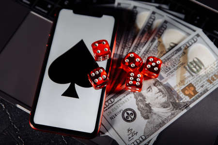 Dice, smartphone and dollar banknotes on keyboard close-up. Online casino concept Stok Fotoğraf