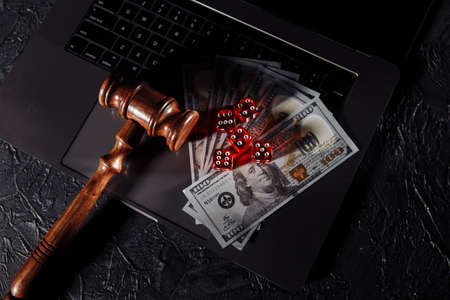 Law and rules for online gambling, judge gavel and dice on keyboard