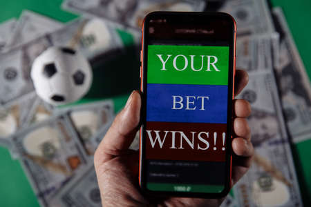 Smartphone with gambling mobile application and soccer ball on green background. Bet wins