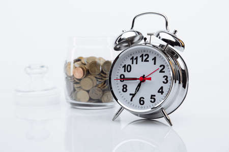 Bank with coins and alarm clock close-up. Time is money concept Stok Fotoğraf