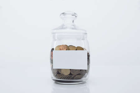 Coins in a glass bank with space for text in a white room. Deposit concept Stok Fotoğraf