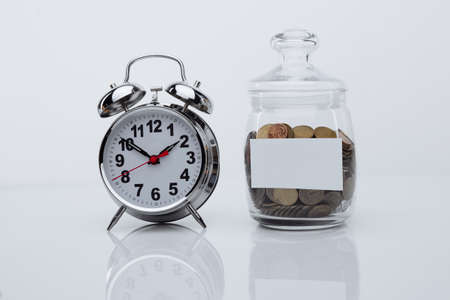 Coins in a glass bank with space for text and alarm clock in a white room. Time is money Stok Fotoğraf