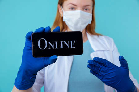 Online appointment to therapist using phone. Female doctor holding mobile to sign up in the Internet. Stok Fotoğraf