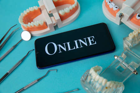 Dentist online appointment. Phone with medical instruments and jaw isolated on the blue background.