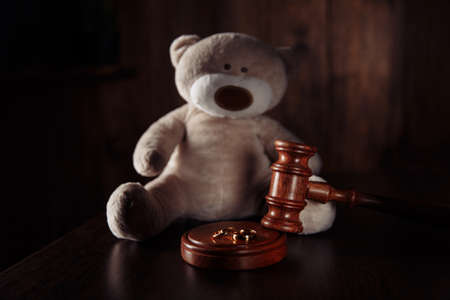 Divorce concept. Wooden gavel, rings and teddy bear as symbol of child. Family divorce effect on children