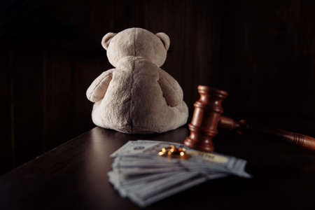 Judge gavel, money banknotes, rings and teddy bear on a wooden table. Divorce, separation and alimony concept