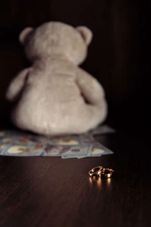 Dollar banknotes, rings and teddy bear close-up. Divorce, separation and alimony concept