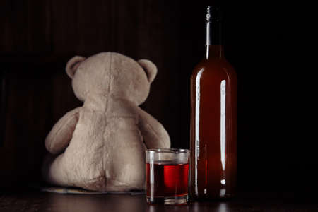 Alcohol and child abuse. Teddy bear as a symbol of childs safety and bottle with glass close-up