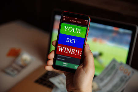 Man holding smartphone with gambling mobile application celebrates victory