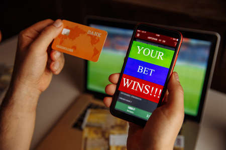 Lucky winner at football betting with credit card and phone in hands close-up Stok Fotoğraf