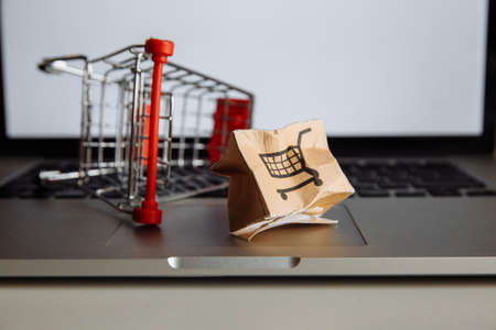 Damaged paper box and shopping cart on a keyboard of laptop close-up. Online shopping, service and delivery concept Stok Fotoğraf