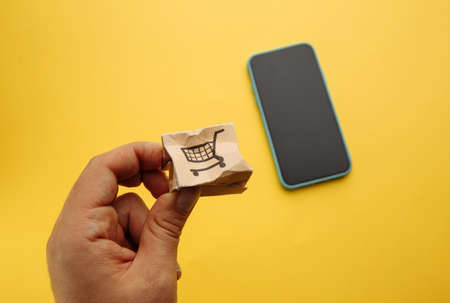 Damaged paper box in males hand near smartphone. Online shopping, service and delivery concept