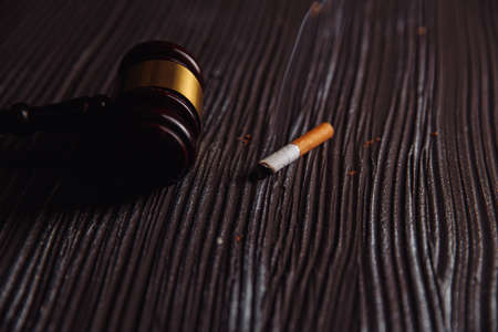 Judge gavel and cigarette on a wooden table. Tobacco law