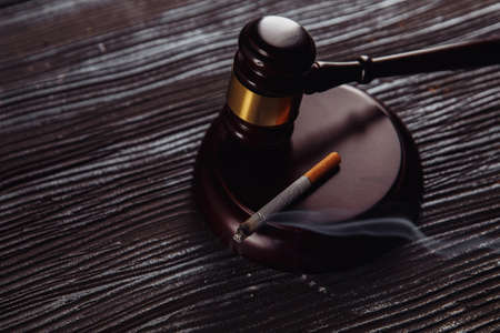 Smoking cigarette and wooden judge gavel close-up. Dangerous addiction