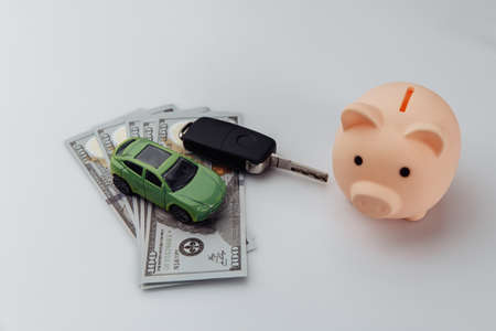 Green car with key, piggy bank and dollar banknotes on a white background. Car loan concept Stock fotó