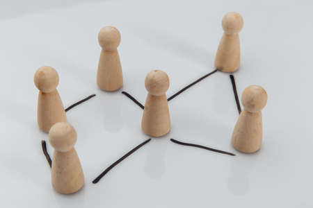 A wooden figures as a symbol of team on white table. Human resources and management concept Stock fotó