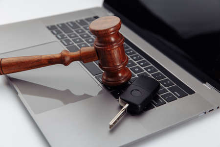 Judge gavel and car keys on laptop computer keyboard. Symbol of law, justice and online car auction