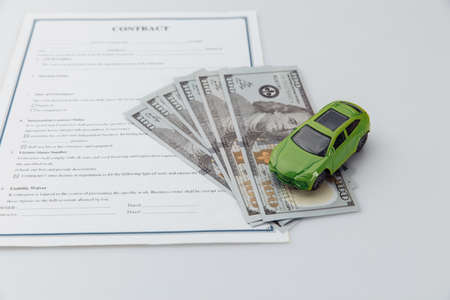 Toy car and contract on a table. Car purcase concept
