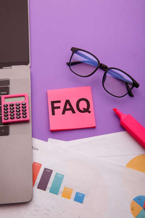Sticky note with word FAQ on pink table. Frequently asked question concept. Vertical image