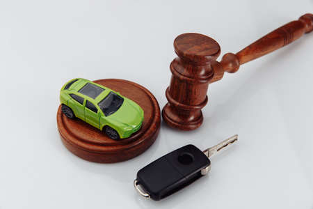 Judge gavel and green toy car with keys on a white table close-up. Symbol of law, justice and car auction