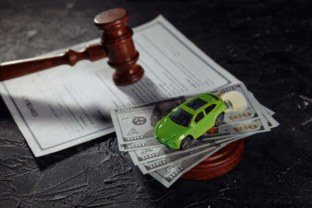 Toy car on dollar banknotes and wooden judge gavel with contract