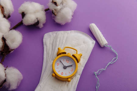Daily sanitary pads, tampon and yellow alarm clock close-up. Hygiene protection for woman critical days