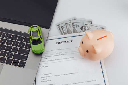 Purchase contract for a car with laptop, piggy bank and toy car