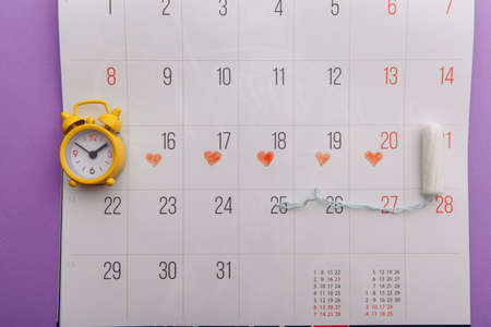 Females menstrual cycle concept. Menstrual period on a calendar with sanitary pads and alarm clock