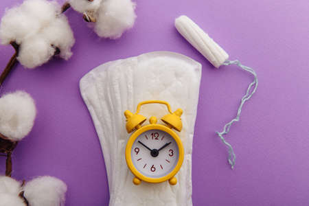 Daily sanitary pads, tampon and yellow alarm clock. Hygiene protection for woman critical days