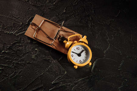 Yellow alarm clock in a mousetrap