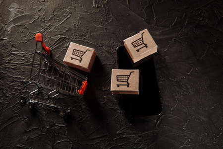 Concept of online shopping. Boxes, shopping cart and smartphone on a grey background