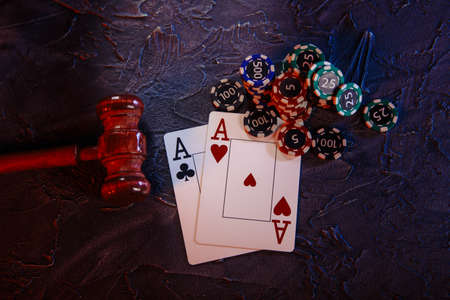 Law and rules for online casino concept, judge gavel with aces and playing chips on a grey background. Top view Stock fotó