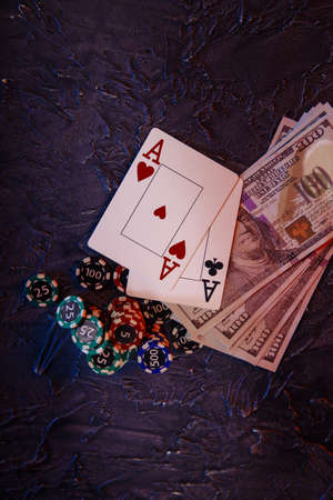 Online casino сoncept. Dollar banknotes, stucks of gambling chips and aces. Vertical image