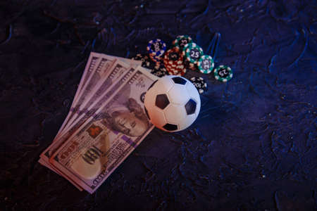Gambling chips, soccer ball and dollar banknotes on a grey background. Online gambling and betting concept Stock fotó
