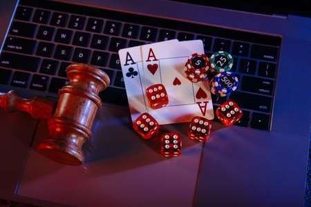 Law for online casino. Wooden judge gavel and aces with playing chips and dices