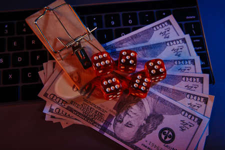 Mousetrap on dollar banknotes and casino dices close-up. Online gambling addiction Stock fotó