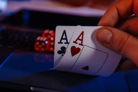 Dices and cards for poker in hand on laptop, online poker concept Stock fotó