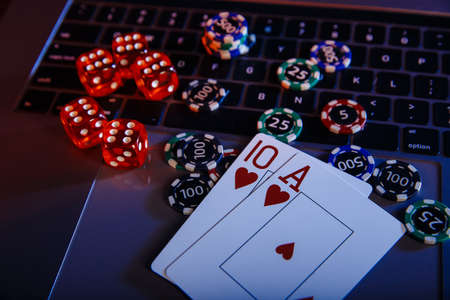 Casino play online theme. Playing chips, cards and dices on laptop close-up Stock fotó