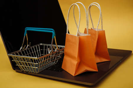 Concept of online shopping. Orange bags and shopping cart on laptop isolated on yellow