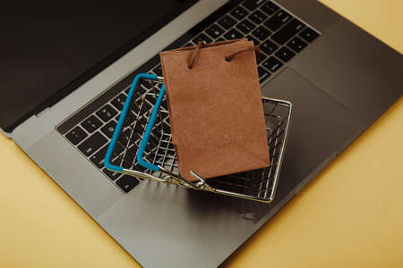 Concept of online shopping. Paper shopping bag and cart on keyboard of laptop isolated on yellow. Top view