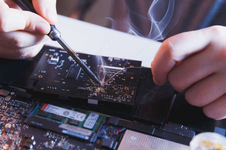 PC technology .Computer repair shop. Engineer performing laptop maintenance. Hardware developer fixing electronic components.