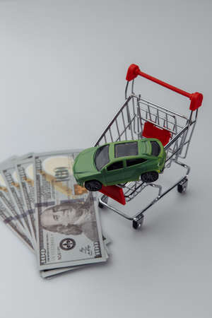 Toy car in a shopping basket and money. Vertical image