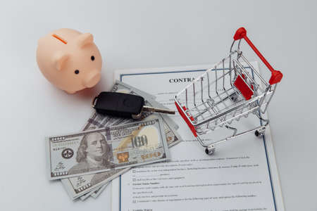 Car keys, dollar banknotes and piggy bank on credit contract