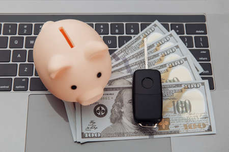 Car key and piggy bank with money on a laptop keyboard